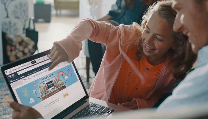 Amazon auf Laptop. Kind zeigt mit Finger darauf