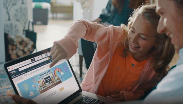 Kind zeigt auf Laptop, Amazon Website geöffnet
