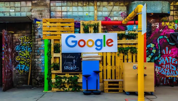 Google Sign vor Paletten und Hauswand