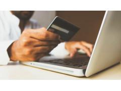 AliExpress soll die neuste E-Commerce-Plattform in Europa werden. Große Marken sind noch skeptisch. Auf dem Bild sieht man einen Laptop und einen Mann, der davor sitzt und eine Kreditkarte in der Hand hat.