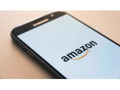 Auf dem Bild ist eine Smartphone zu sehen, auf dessen Bildschirm das Amazon Logo zu sehen ist.