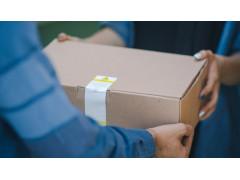 Auf dem Bild sieht man einen Mann, der einer Frau einen Pappkarton überreicht. Mit den Plus-Produkten auf Amazon können auch kleine Einkäufe direkt nach hause geliefert werden