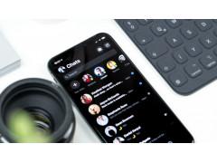 Facebook Messenger: Ein Handy liegt auf einem weißen Tisch. Auf dem Desktop sieht man verschiedene Chats.