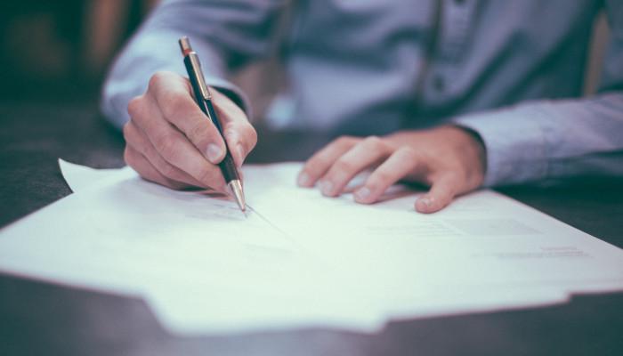 NetzDG: Bußgeld für Facebook. Auf dem Bild sieht man viele verschiedene Papierblätter auf einem dunkelen Schreibtisch verteilt. Die Unterarme und Hände eines Mannes sind zu sehen, der einen Stift in den Händen hält.