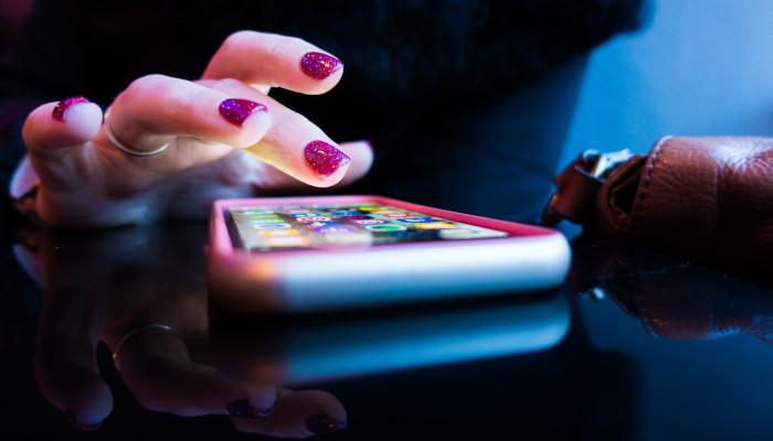 Auf dem Bild ist eine hand mt lakierten Nägeln zu sehen, die auf ein Smartphone Screen tippt.