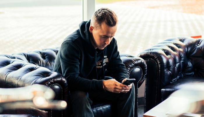 Mann sitzt mit Smartphone auf Ledersessel