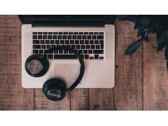 Spotify Podcast Ads ermöglichen personlaisierte Werbung: Auf dem Bild sieht man einen Laptop auf einem Tisch. auf der Tastatur liegen Kopfhörer