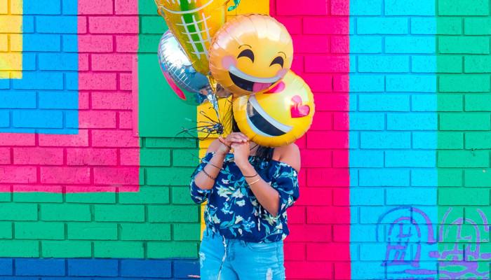 Frau versteckt sich hinter bunten Luftballons