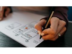 Marketing Automation, Stift in Hand malt auf Papier.