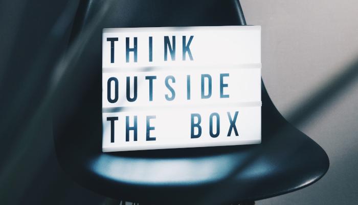 Schild auf Stuhl, Think Outside the Box
