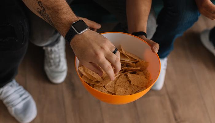 Hände an Schüssel mit Chips