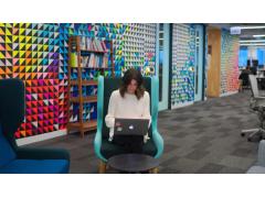 Frau vor Laptop in Büroraum