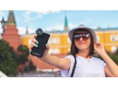 Frau mit Smartphone vor Stadthintergrund.