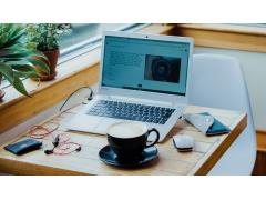 Laptop und Tasse auf Tisch