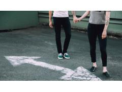 Zwei Personen halten sich an der Hand vor weißem Pfeil auf Boden