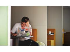 Mann mit Laptop an Tisch, Kopf in die Hand gestützt.