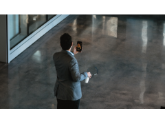 Mann mit Smartphone im Video Chat in einem leeren Flur.