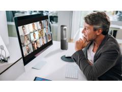 Ein Mann sitzt an einem Schreibtisch und schaut auf einen Bildschirm, auf dem ein Zoom Meeting stattfindet