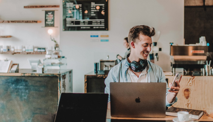 Ein Mann sitzt in einem Café vor dem Laptop