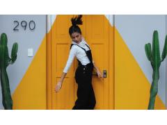 Frau springt vor gelb bemalter Tür zwischen Kakteen