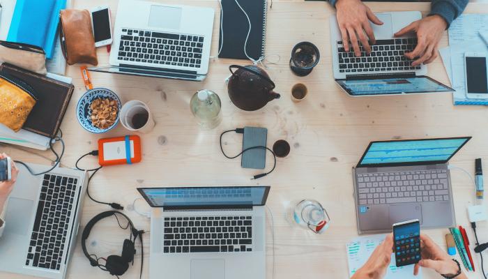 Laptops und Gerätschaften auf einem Tisch, Hände bedienen Smartphone und Tablet