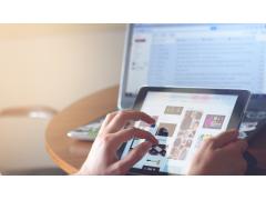 Hände tippen auf Tablet, Desktop im Hintergrund
