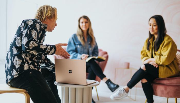Der Menschen sitzen um einen Laptop