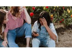 Drei junge Frauen, die auf ein Smartphone schauen