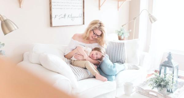 Frau und Kind sitzen lachend auf dem Sofa