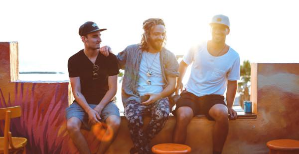 Drei Männer sitzen lachend nebeneinander
